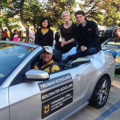 Mizzou students and scholarship recipients Emily Cheng, Emily Waggoner and Brendan Marsh join MU Director of Fellowships Tim Parshall in the 2015 Homecoming Parade.